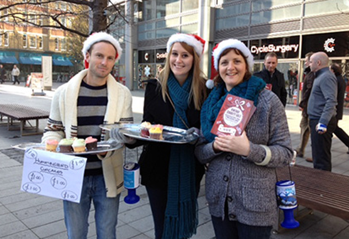 Three people selling cakes